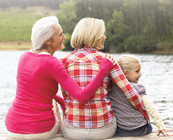 grandma, mother, and daughter sitting on a dock